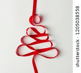 Small photo of Christmas tree made of red satin ribbon. New Year Christmas minimal greeting card background. Flat lay.