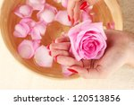 woman hands with wooden bowl of water with petals - stock photo