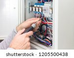 electrician at work on an electrical panel - stock photo