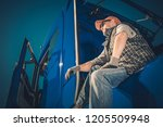 Truck Driver Cargo Transport. Caucasian Men Seating on His Semi Tractor and Enjoying the View. - stock photo