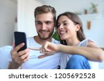young couple watching online... | Shutterstock . vector #1205692528