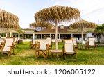 straw umbrellas with sunbeds on ... | Shutterstock . vector #1206005122