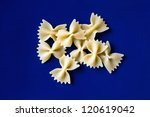 Dry farfalle pasta on blue background - stock photo