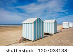 striped beach cabins at... | Shutterstock . vector #1207033138