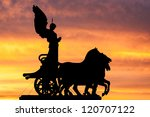 Rome at dusk: silhouette of the goddess Victoria over the National Monument to Vittorio Emanuele II - stock photo