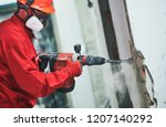worker with demolition hammer removing plaster or stucco from wall - stock photo