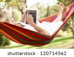 Small photo of Senior Woman Relaxing In Hammock With E-Book