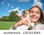 girl hugging her dog and laughs ... | Shutterstock . vector #1207613065