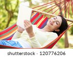 Small photo of Woman Relaxing In Hammock With E-Book