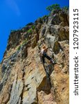 young man climbing a cliff with ... | Shutterstock . vector #1207923115