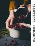 female hands pouring ripe... | Shutterstock . vector #1208235952