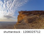 Hikers Atop a Cliff Await the Sunset under a Blue Sky and White Clouds, Edge of the World, Riyadh, Saudi Arabia - stock photo