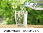 pouring water from bottle into... | Shutterstock . vector #1208349172