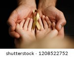 Small photo of golden ribbon childhood symbol of the fight against cancer in children in hands on a dark background. concept of helping patients with sarcoma and bladder cancer