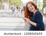 Small photo of Pretty young redhead woman with a happy smile standing leaning on a low wall in a quiet urban street holding a mobile phone