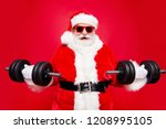 Small photo of Portrait of stylish virile strong muscular sporty Saint Nicholas in eyeglasses gloves fur white red winter coat clothes holding lifting two big dumbbells in arms striving isolated on red background
