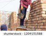 worker builds a brick wall in... | Shutterstock . vector #1209151588