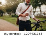 businessman holding a coffee... | Shutterstock . vector #1209431365