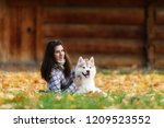 Stock photo girl plays with her husky dog in fallen autumn leaves 1209523552