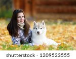 Stock photo girl plays with her husky dog in fallen autumn leaves 1209523555