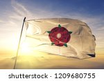 Lancashire county of England flag textile cloth fabric waving on the top sunrise mist fog