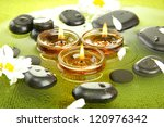 spa stones with flowers and candles in water on plate - stock photo
