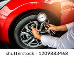 Small photo of Asian man car inspection Measure quantity Inflated Rubber tires car.Close up hand holding machine Inflated pressure gauge for car tyre pressure measurement for automotive, automobile image