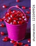Sweet ripe pomegranate seeds in decorative bucket. - stock photo