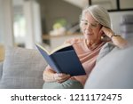 senior woman reading on couch... | Shutterstock . vector #1211172475