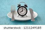 clock on white plate with fork... | Shutterstock . vector #1211249185