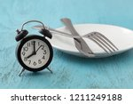 clock with white plate  fork... | Shutterstock . vector #1211249188
