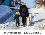 woman with child go on a snowy... | Shutterstock . vector #1211284552
