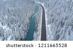 AERIAL: White car drives down empty road running along the beautiful emerald river in the cold Californian winter. Tourists on road trip cruising through the idyllic snow covered countryside and woods