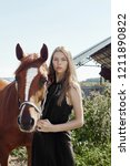 girl rider stands next to the... | Shutterstock . vector #1211890822