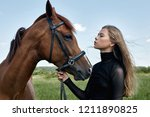 girl rider stands next to the... | Shutterstock . vector #1211890825