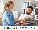 female nurse preparing male... | Shutterstock . vector #1212110755