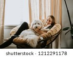 woman and her dog at home | Shutterstock . vector #1212291178