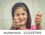 Small photo of Smiling little girl showing ice cream stick. Young kid portrait on pink t shirt with full mouth after eating cold dessert. Dirty, mess, fun, childhood joy concepts