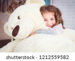 A Child Is Hugging A Big Teddy...