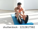 muscular man stretches at the...   Shutterstock . vector #1212817582