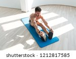 muscular man stretches at the...   Shutterstock . vector #1212817585