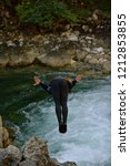 man jumping in wild river... | Shutterstock . vector #1212853855