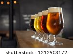 Stock photo glasses with different sorts of craft beer on wooden bar tap beer in pint glasses arranged in a 1212903172