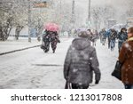 Small photo of the city was covered by a snow storm, cold, climate change, movement is paralyzed because of the snow people move to the snowstorm on foot, hiding umbrellas and hoods, abnormal winter, precipitation