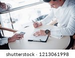 young man signs documents in... | Shutterstock . vector #1213061998
