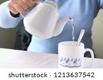 woman pouring hot water from... | Shutterstock . vector #1213637542