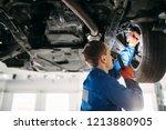 mechanic with lamp checks car... | Shutterstock . vector #1213880905