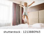 little girl jumping on the bed... | Shutterstock . vector #1213880965