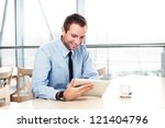 Businessman with digital tablet smiling - stock photo