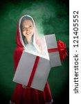 Smiling female Santa opening the magic Christmas present box on dark green background - stock photo